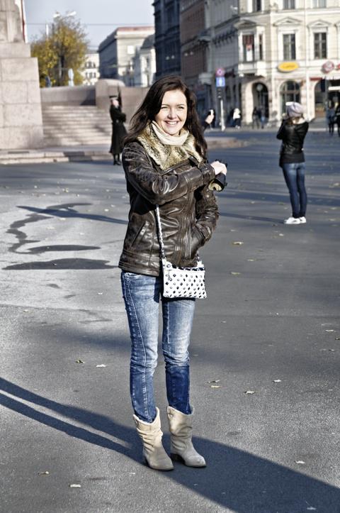 Bild: Junge Frau am Freiheitsdenkmal in Riga.
