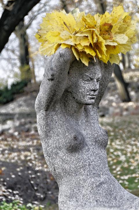 Bild: Blumengeschmückte Statue im Park am Stadtkanal von Riga.