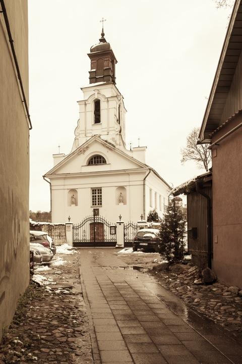 Bild: Die Kirche im meist von Künstlern oder Alternativen bewohnten Stadtteil Užupis. Diese Stadtteilkirche ist dem Heiligen Bartholomäus geweiht. Sie liegt etwas versteckt hinter einer Häuserfront am Abhang zum Flüsschen Vilnelė. NIKON D700 mit AF-S NIKKOR 28-300 mm 1:3.5-5.6G ED VR.