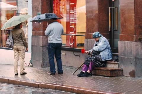Fototour: Unterwegs an einem regnerischen Sommerabend in der Altstadt von Tallinn. Trotz des Wetters versucht diese ältere Frau, in der Vana Viru ein paar Cent zu bekommen. NIKON D700 und AF-S NIKKOR 24-120 mm 1:4G ED VR.