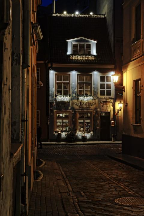 Bild: Abends unterwegs in der Altstadt von Riga in der Krāmu iela mit dem Restaurant Zur Blauen Kuh. NIKON D700 mit AF-S NIKKOR 24-120 mm 1:4G ED VR. ISO 2000 ¦ f/7,1 ¦ 55 mm ¦ 1/25 s ¦ kein Blitz. Klicken Sie auf das Bild um es zu vergrößern.