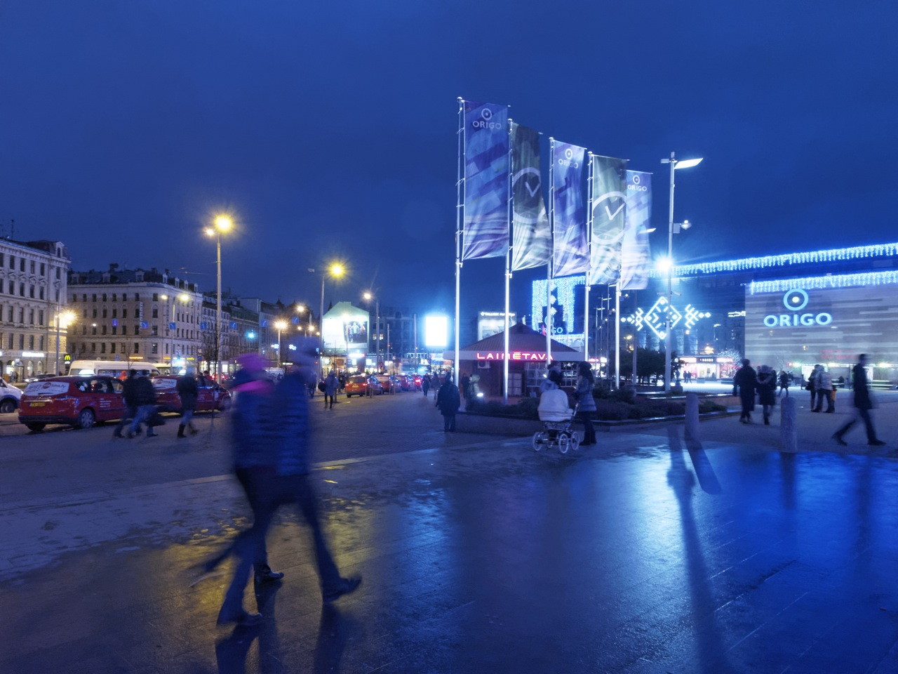 Bild: In der Vorweihnachtszeit abends unterwegs am Einkaufszentrum ORIGO am Hauptbahnhof von Riga. OLYMPUS OM-D E-M5 mit M.Zuiko Digital 12-50 mm 1:3.5-6.3 EZ. ISO 6400 ¦ f/9 ¦ 12 mm ¦ 1/10 s ¦ kein Blitz. Klicken Sie auf das Bild um es zu vergrößern.