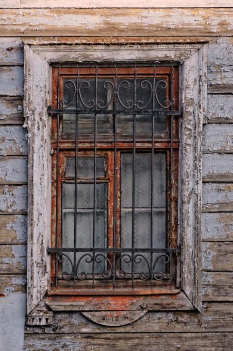 Bild: Fenster an einem verlassenen Holzhaus in der Moskauer Vorstadt in Riga. Bürokraten können alles unter den Schirm des Weltkulturerbes stellen. Wenn die Bewohner wegen mangelnder Perspektive abwandern, hilft das aber auch nicht. NIKON D300s mit AF-S DX NIKKOR 18-200 mm 1:3.5-5.6G ED VR Ⅱ. ISO 200 ¦ f/5,6 ¦ 112 mm ¦ 1/30 s ¦ kein Blitz. Klicken Sie auf das Bild um es zu vergrößern.