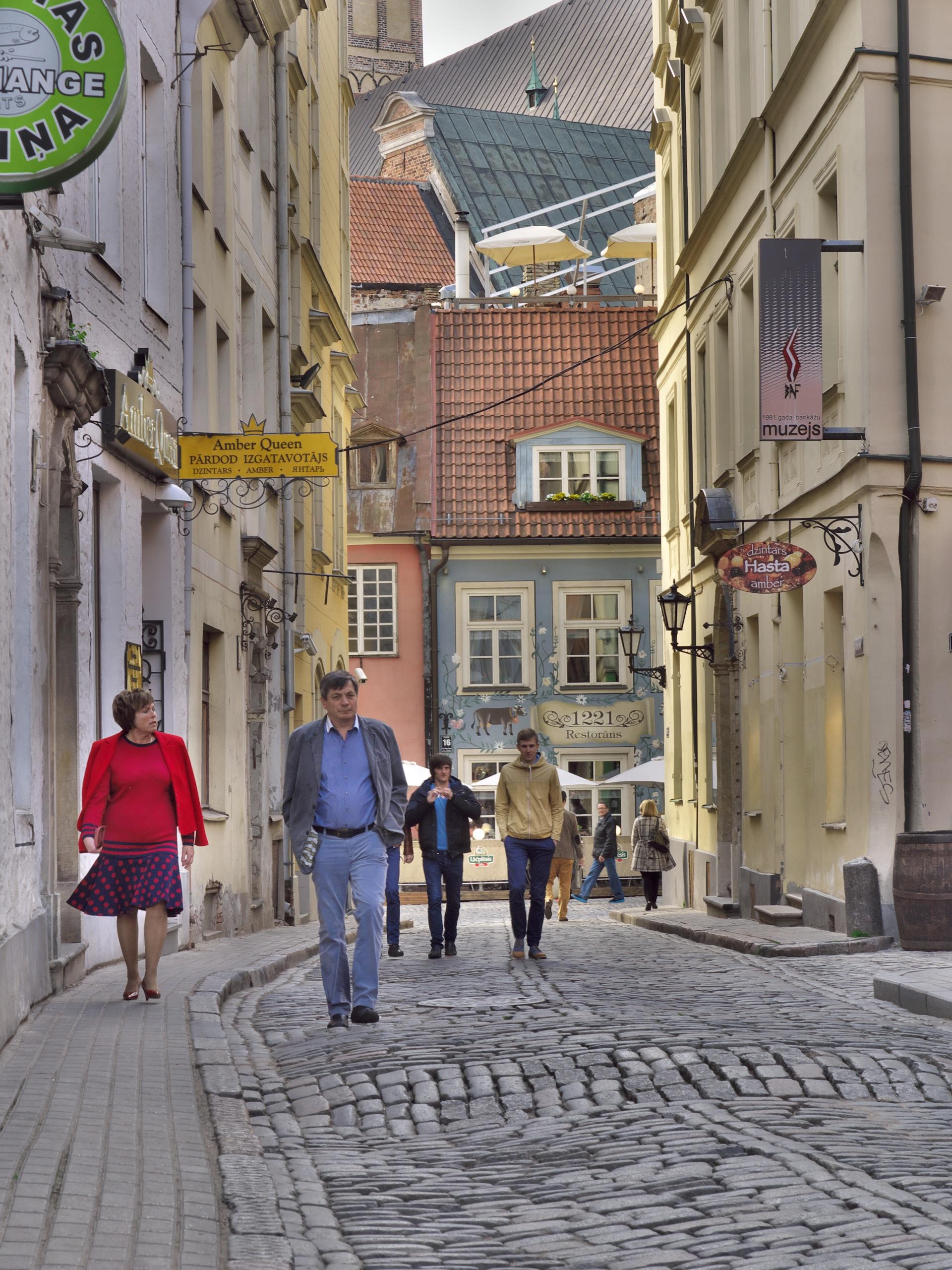 Bild: Eine der schönsten Gassen in der historischen Altstadt von Rīga ist die Tirgoņu iela, die am Restaurant Zur Blauen Kuh endet. Im Hintergrund ist der mächtige Dom von Rīga zu sehen. OLYMPUS OM-D E-M5 mit M.ZUIKO DIGITAL ED 12‑40mm 1:2.8. ISO 200 ¦ f/9 ¦ 40 mm ¦ 1/40 s ¦ kein Blitz. Klicken Sie auf das Bild um es zu vergrößern.