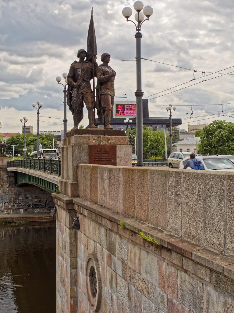 Bild: Die Grüne Brücke in Vilnius ist wegen ihrer Bronzestatuen aus sowjetischer Zeit heute sehr umstritten. Der Kontrast zum modernen Vilnius ist in der Tat sehr groß. OLYMPUS OM-D E-M1 mit M.ZUIKO DIGITAL ED 12‑40mm 1:2.8 ISO 200 ¦ f/7,1 ¦ 25 mm ¦ 1/320 s ¦ kein Blitz. Klicken Sie auf das Bild um es zu vergrößern.