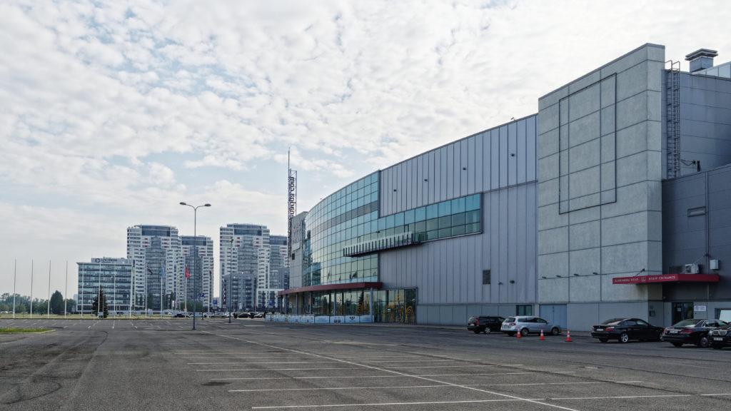 """Bild: Die Mehrzweckhalle Arēna Rīga im Stadtteil Skanste von Rīga. Im Hintergrund sind die vier Hochhäuser """"Skanstes virsotnes"""" zu sehen."""