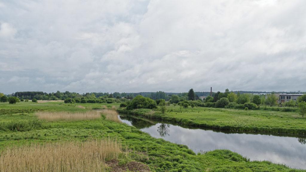 Bild: Blick in das Tal des Flusses Abava in Kandava in Lettland. Im Hintergrund sind verfallene Industriebetriebe zu sehen, die in Lettland bis heute allgegenwärtig sind.
