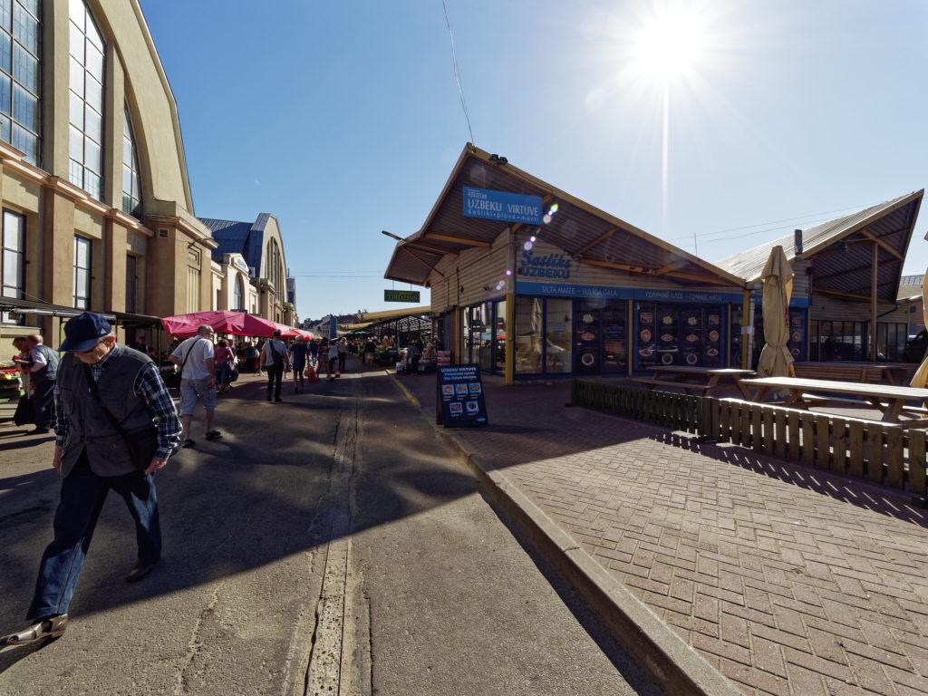 Bild: Auf dem Außengeländes des Zentralmarktes von Rīga. Ende Mai 2018. Hier gibt es auch was zum Essen. Usbekisches Restaurant mit leckerem Lagman. OLYMPUS OM-D E-M1 Mark II mit M.ZUIKO DIGITAL ED 7‑14mm 1:2.8 PRO. Klicken Sie auf das Bild, um es zu vergrößern.