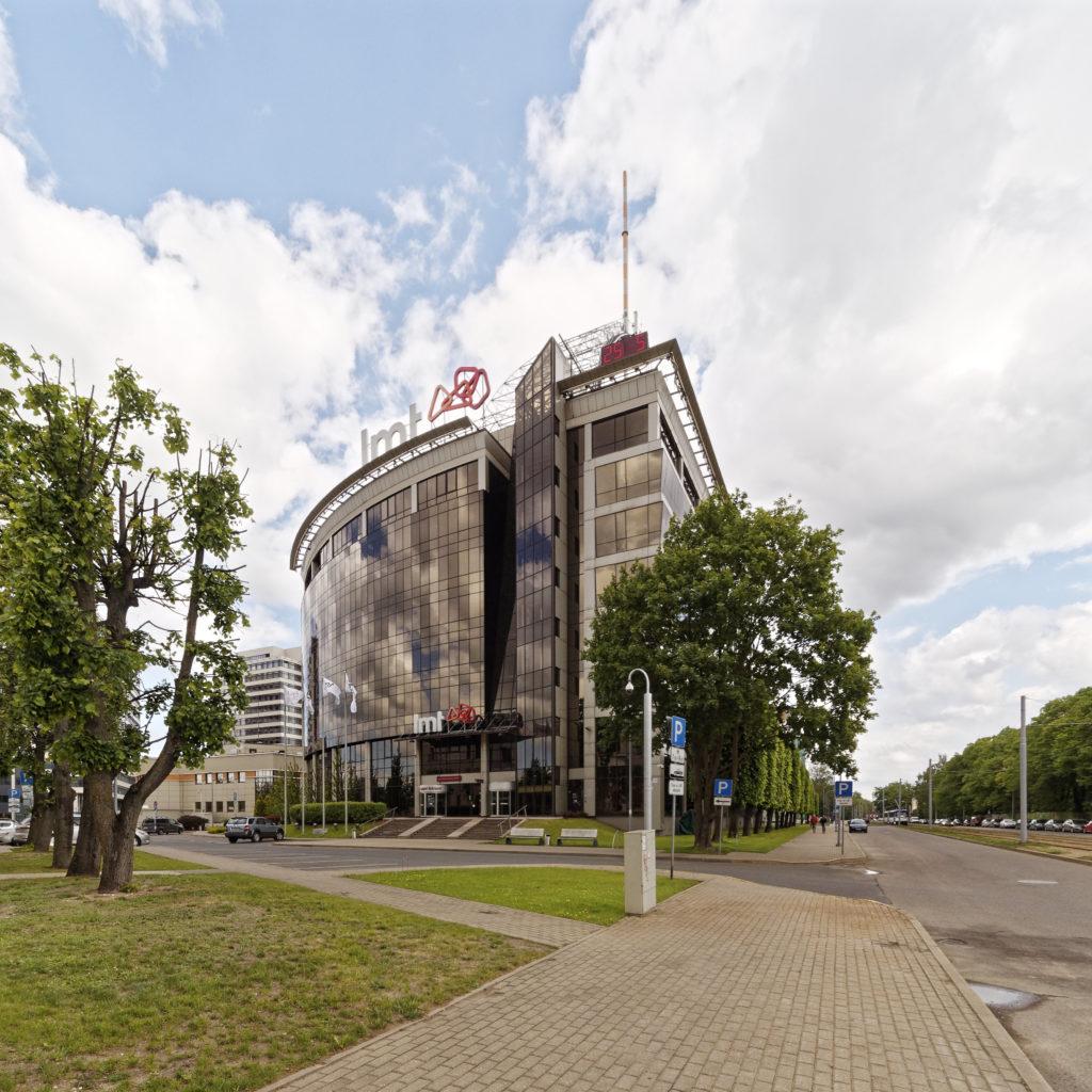 Bild: Bürogebäude der lettischen Telefongesellschaft LMT am Kulturhaus des ehemaligen Unternehmens VEF (Valsts elektrotechniskā fabrika; deutsch: Staatliche Elektrotechnische Fabrik) an der Brīvības gatve im Stadtteil Teika von Rīga. Das Gebäude wurde 2001 errichtet. Aufnahme aus dem Jahr 2019.
