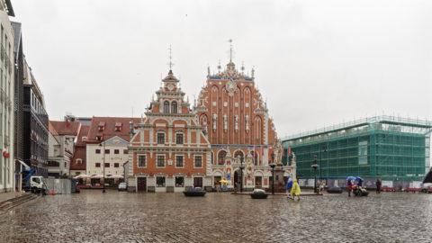 Bild: Auf dem Rathausplatz der Altstadt von Rīga. Von links nach rechts sind die Gebäude Speicher der Blauen Garde, das Schwabehaus und das Schwarzhäupterhaus zu sehen. Ganz rechts im Bild ist das gerade in der Rekonstruierung befindliche Lettische Okkupationsmuseum zu sehen.
