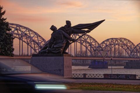 Bild: Sonnenuntergang an einem Novemberabend am Altstadtufer der Daugava in Rīga. Im Bild sind das Denkmal zu Ehren der Revolution von 1905 und die Eisenbahnbrücke zu sehen. Klicken Sie auf das Bild um es zu vergrößern.