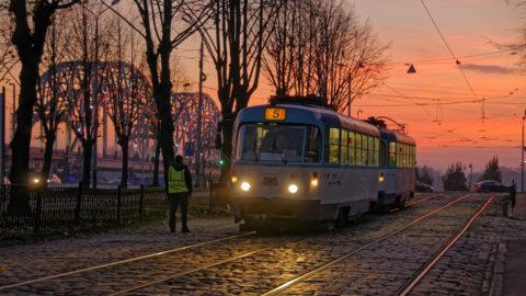 Bild: Sonnenuntergang an einem Novemberabend am Altstadtufer der Daugava in Rīga. Im Bild ist die Vorbereitung einer Fahrkartenkontrolle in einer Straßenbahn zu sehen. Fahrkartenkontrollen sind in Rīga immer generalstabsmäßig organisiert. Klicken Sie auf das Bild um es zu vergrößern.