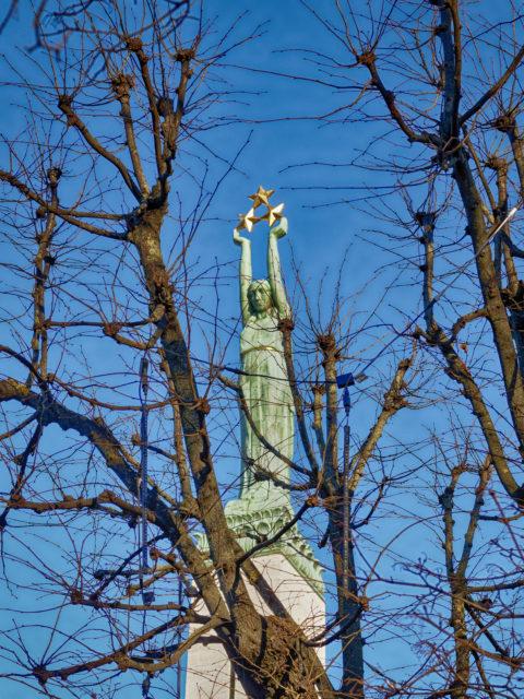 Bild: Das Freiheitsdenkmal - lettisch Brīvības piemineklis - auf dem Brīvības bulvāris in Rīga. Blick auf die Mädchenfigur Milda mit den drei Sternen, die die drei Regionen Lettlands - Vidzeme, Latgale und Kurzeme - symbolisieren. OLYMPUS PEN-F mit SIGMA 60 mm F2.8 DN ART -ISO200 ¦ f/5,6 ¦ 60 mm ¦ 1/800 s ¦ kein Blitz. Klicken Sie auf das Bild um es zu vergrößern.